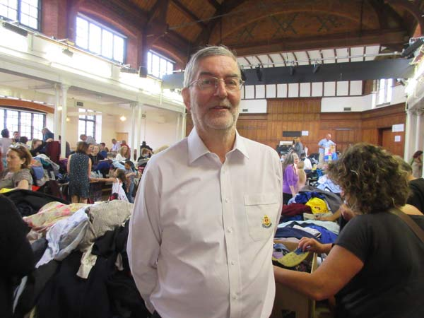 Alan King, head leader of 1st Barnet Boys' Brigade and Girls' Association, taking command as bargain hunters crowd around during the summer jumble sale
