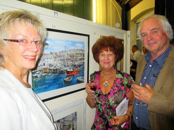 Barbara Gladding (centre), a long-standing member of the Barnet Guild of Artists, with her watercolour of Mevagissey, one of her five painting on display at the Guild's 68th annual exhibition. With her are friends, Elaine Padmore and Grant Shelley