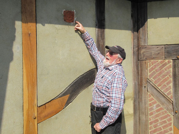 Mike Jordan, former chair of Barnet Museum trustees, pointing to one of the early tiles in the mock-Tudor façade of Barnet Physic Well.