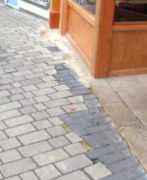 The workmanship of pavement repairs at the entrance to Guns and Smoke typifies the casual approach to this site by both the landlord and tenant