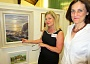 Nichola Peasnell, chair of the Barnet Guild of Artists (left), shows the Chipping Barnet MP Theresa Villiers an oil painting, Staithes Sunrise, chosen as the poster illustration for the Guild's 68th annual exhibition
