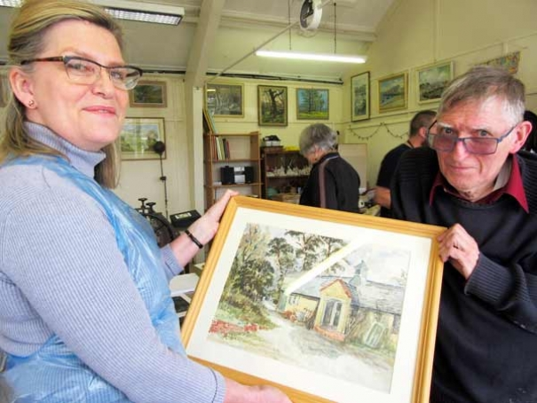 Fred Howett (left) with Nichola Hunt, chair of the Barnet Guild of Artists, admiring a water colour of the Whalebones stable block by the late Miss Gwyneth Cowing who promised that the guild would have the continued use of its studio on the Whalebones estate.