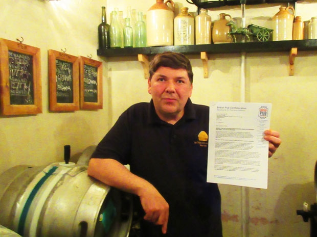 "Gary Murphy in the cellar of The Mitre with a letter from the British Pub Confederation praising his ""courage and tenacity"""