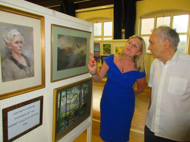 A portrait of founder Gwyneth Cowing and some of her paintings are admired by Nichola Hunt, chair of the Barnet Guild of Artists and guild secretary Bryan Polikoff