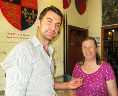 Sam Wilson, military archaeologist, shows Dorothy Cohen, the medieval penny that was found with metal detectors in the latest search of a likely site of the Battle of Barnet