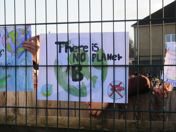 Children show their posters at the school gate