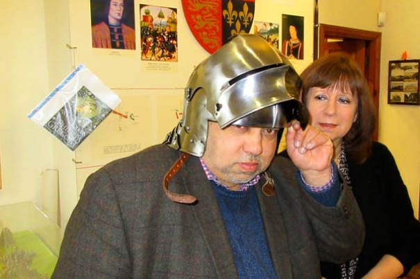 Hilary Harrison, a member of the Battle of Barnet project team, looks on as trustee Michael Noronha tries out a medieval helmet newly acquired by Barnet Museum.