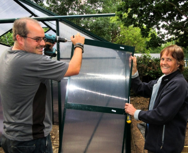 Maria Wright helps her son Derek with the new greenhouse at the Pavilion study centre