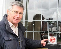 "CAMRA's David Fenton pointing to the forlorn sign ""This pub matters"" – the only remaining reminder of what was once the White Lion public house"